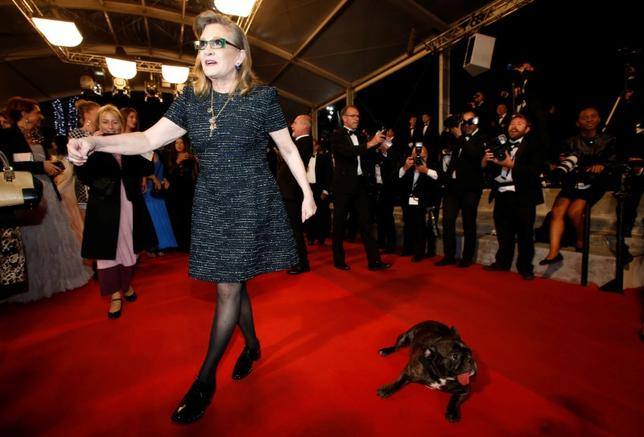 Actress Carrie Fisher arrives with her dog on the red carpet for the screening of the film