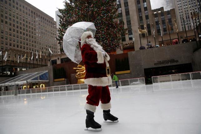 A man dressed as Santa Claus ice skates at The Rink At Rockefeller Center on Christmas Eve in Manhattan, New York City, U.S., December 24, 2016. REUTERS/Andrew Kelly