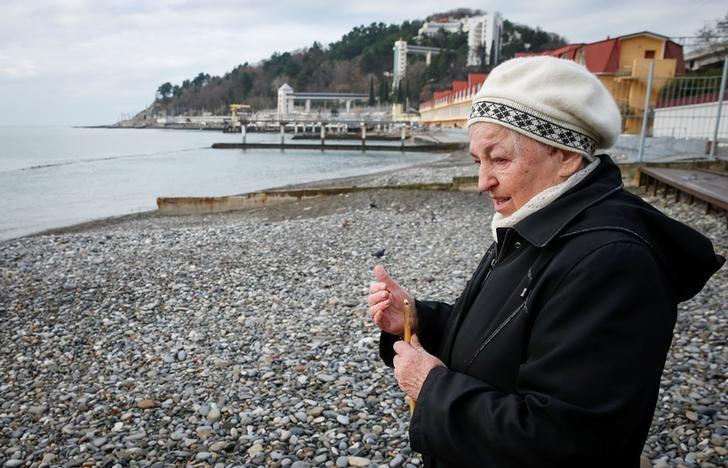 A woman holds a candle as she stays on a coastline next to the crash site of a Russian military Tu-154 plane, which crashed into the Black Sea on its way to Syria on Sunday, in the Black Sea resort city of Sochi, Russia, December 26, 2016. REUTERS/Maxim Shemetov