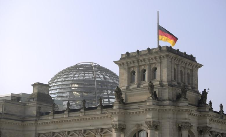 German flag flutters half-mast on top of the Reichstag building, the seat of the German lower house of parliament Bundestag in Berlin, March 25, 2015. REUTERS/Stefanie Loos