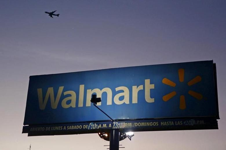 Aircraft flies over a Wal-Mart billboard in Mexico City March 24, 2015. REUTERS/Edgard Garrido/File Photo      - RTSLSIY