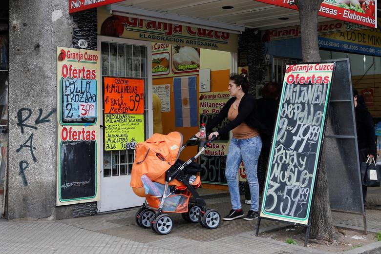 A woman pushing a baby carriage walks past a shop selling farm products in Buenos Aires July 31, 2014.    REUTERS/Enrique Marcarian/File Photo