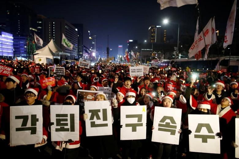 People dressed in Santa's costumes attend a protest demanding South Korean President Park Geun-hye's resignation in Seoul, South Korea, December 24, 2016. The banner reads ''Resign immediately, Arrest investigation''.  REUTERS/Kim Hong-Ji