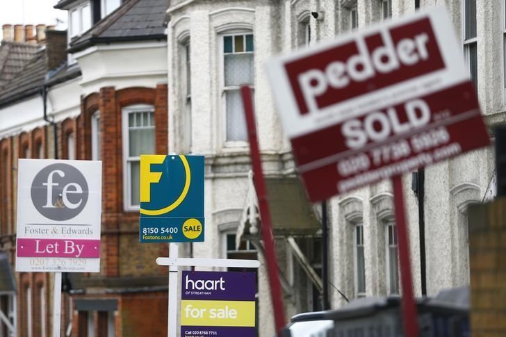 Estate agents boards are lined up outside houses in south London June 3, 2014. REUTERS/Andrew Winning/Files