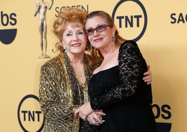 Actress Debbie Reynolds poses with her daughter actress Carrie Fisher backstage after accepting her Lifetime Achievement award at the 21st annual Screen Actors Guild Awards in Los Angeles, California January 25, 2015.  REUTERS/Mike Blake/File Photo