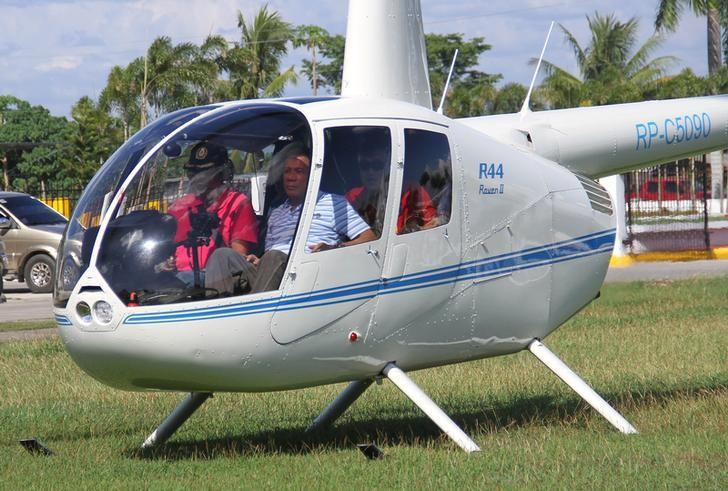 Then-local mayor of Davao city Rodrigo Duterte (R), aboard a helicopter, arrives at the provincial capitol in Tagum city, Davao del Norte, southern Philippines for the Regional Peace and Order Council meeting, April 20, 2015. REUTERS/Lean Daval Jr./Files