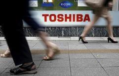 Las acciones de Toshiba cayeron más del 19 por ciento el jueves, en su tercer día de fuertes pérdidas después de que el conglomerado tecnológico y nuclear japonés dijese esta semana que se enfrentaba a un eventual ajuste por deterioro de activos de miles de millones de dólares. En la imagen, varios peatones pasan junto a un cartel de Toshiba en Tokio el 14 de septiembre de 2015.   REUTERS/Toru Hanai/File Photo
