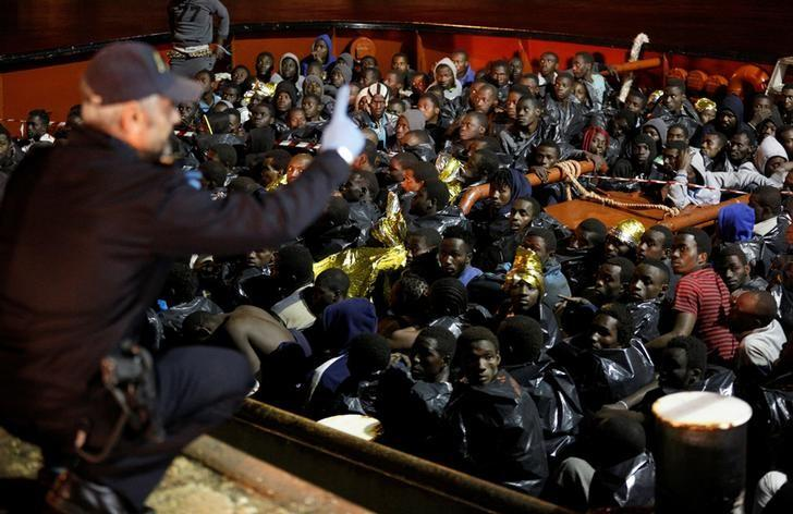 Migrants wait to disembark from a vessel in the Sicilian harbour of Augusta, Italy, December 14, 2016. REUTERS/Antonio Parrinello/File Photo
