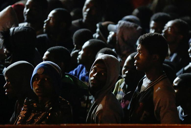 Migrants wait to disembark from a vessel in the Sicilian harbour of Augusta, Italy. REUTERS/Antonio Parrinello