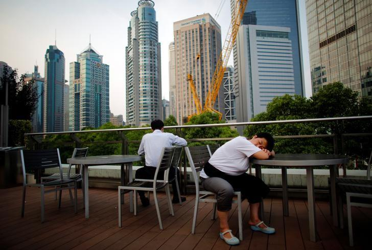 A waitress sleeps as she take a break at a restaurant located in the Pudong financial district of Shanghai July 8, 2013.   REUTERS/Carlos Barria