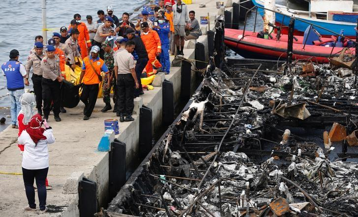 ATTENTION - VISUAL COVERAGE OF SCENES OF INJURY OR DEATHSecurity forces, Red Cross and rescue workers carry body bags with the remains of victims after a fire ripped through a boat carrying tourists to islands north of the capital, at Muara Angke port in Jakarta, Indonesia January 1, 2017.  REUTERS/Darren Whiteside