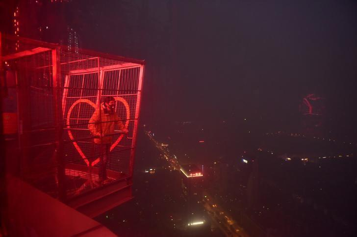 A man stands on a view point on top of a TV tower in heavy smog during a polluted day in Chengdu, Sichuan province, December 20, 2016. Picture taken December 20, 2016. REUTERS/Stringer/Files
