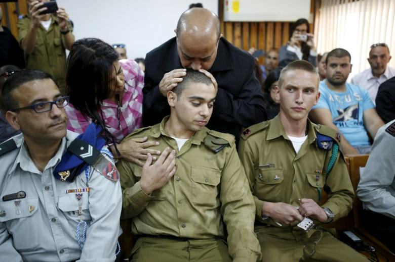 The father of Israeli soldier Elor Azaria, who is charged with manslaughter by the Israeli military after he shot a wounded Palestinian assailant as he laid on the ground in Hebron, kisses Elor's head in a military court during a remand hearing for his case, near the southern Israeli city of Kiryat Malachi, March 31, 2016. REUTERS/Amir Cohen/File Photo
