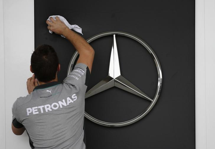 A Mercedes Formula One crew member cleans their team logo in Suzuka, western Japan, October 2, 2014. REUTERS/Toru Hanai/Files
