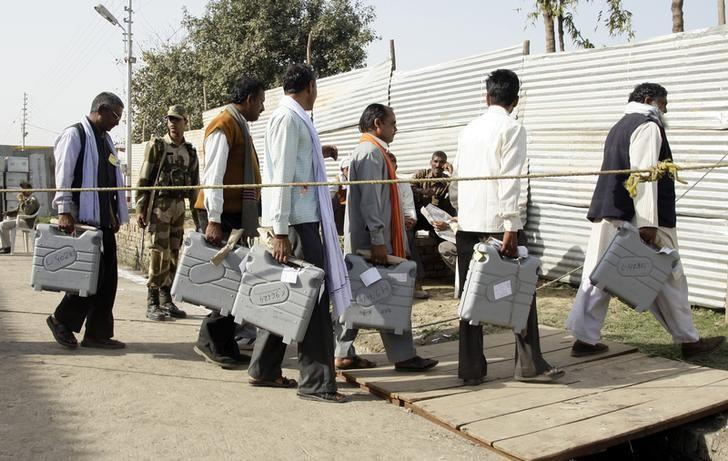 Election officials carry electronic voting machines (EVMs) as they arrive to count ballots at a counting centre in Allahabad March 6, 2012. REUTERS/Jitendra Prakash/Files
