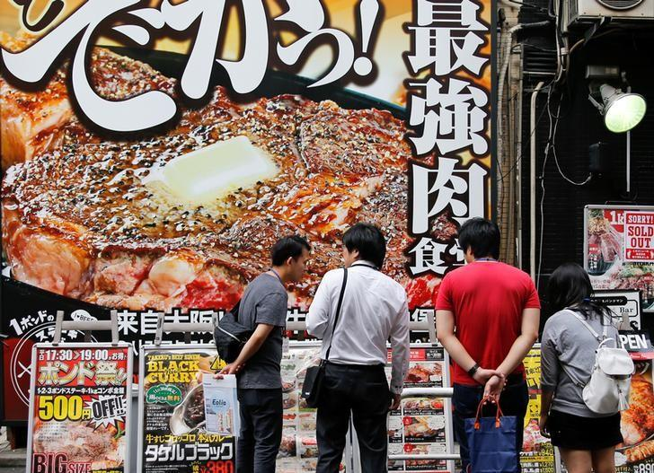 People look at advertisements of restaurants in Tokyo, Japan, October 4, 2016.    REUTERS/Toru Hanai