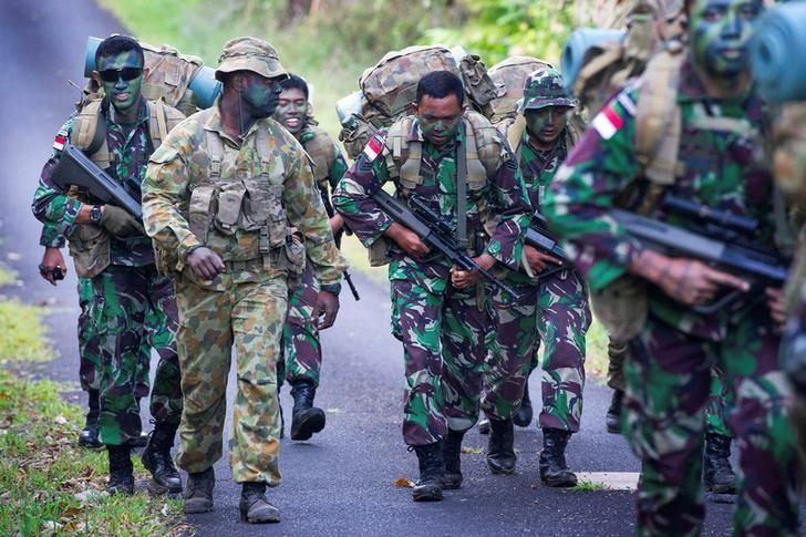Australian Army soldier Sergeant Francis Jakis (L) is pictured with Indonesian Army soldiers during the Junior Officer Combat Instructor Training course conducted by the Australian Army's Combat Training Centre in Tully, Australia, October 10, 2014. Australian Defence Force/Handout via REUTERS