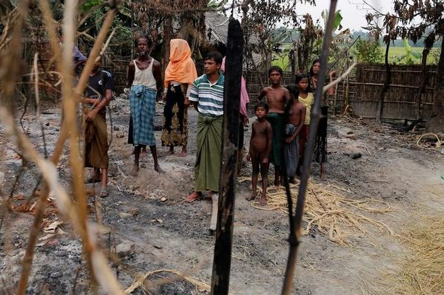 A family stands beside remains of a market, which was set on fire in Rohingya village, outside Maungdaw in Rakhine state, Myanmar October 27, 2016. REUTERS/Soe Zeya Tun/Files