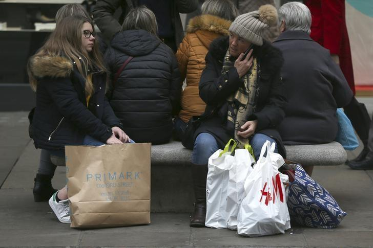 Shoppers rest on a bench with their bags on Oxford Street in London, Britain December 18, 2016. REUTERS/Neil Hall/Files