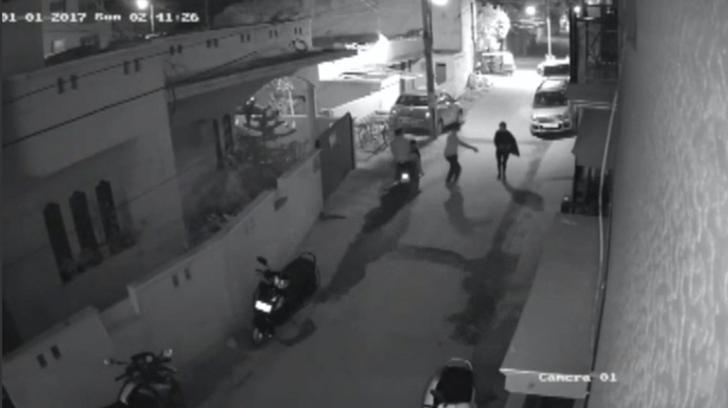 Two men on a scooter assault a woman, attempting to take off her clothes and pushing her to the ground before leaving, in Bengaluru, India, in this still image taken from January 1, 2017 CCTV footage. Local Resident CCTV footage/via Reuters TV