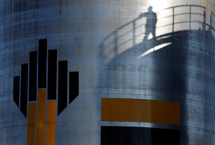 The shadow of a worker is seen next to the logo of Russia's Rosneft oil company at the central processing facility of the Rosneft-owned Priobskoye oil field outside the city of Nefteyugansk, Russia, August 4, 2016. REUTERS/Sergei Karpukhin/File Photo