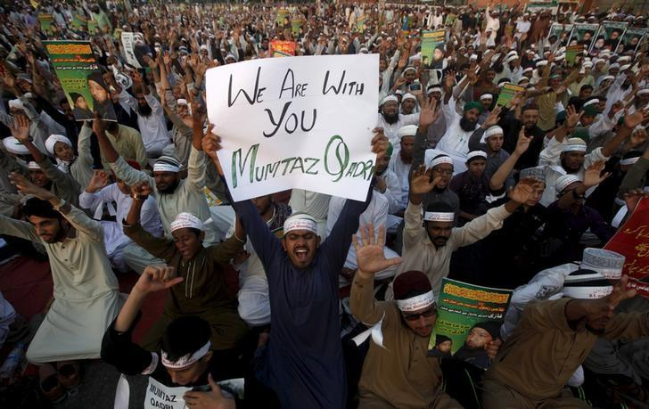 A supporter of the Ahle Sunnat religious political group holds a sign in support of convicted killer Mumtaz Qadri during a sit-in protest demanding his release in Karachi, Pakistan November 20, 2015. In 2011, Salman Taseer, the governor of Punjab, was shot dead by a bodyguard, Mumtaz Qadri, after he had sought a presidential pardon for Asia Bibi, a Christian woman accused of blasphemy.   REUTERS/Athar Hussain