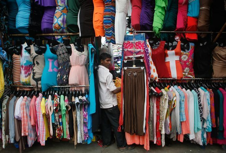 A salesman waits for customers at a roadside store selling clothes at a market in Mumbai September 11, 2013. REUTERS/Danish Siddiqui/Files