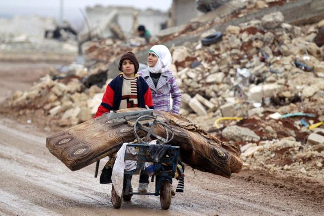 Samah, 11, and her brother, Ibrahim, transport their salvaged belongings from their damaged house in Doudyan village in northern Aleppo Governorate, Syria, January 2, 2017.  REUTERS/Khalil Ashawi
