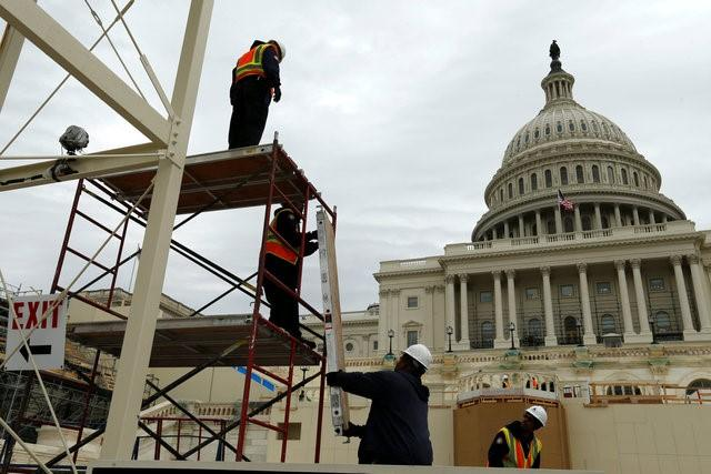 Workers construct the viewing stands ahead of U.S. President-elect Donald Trump