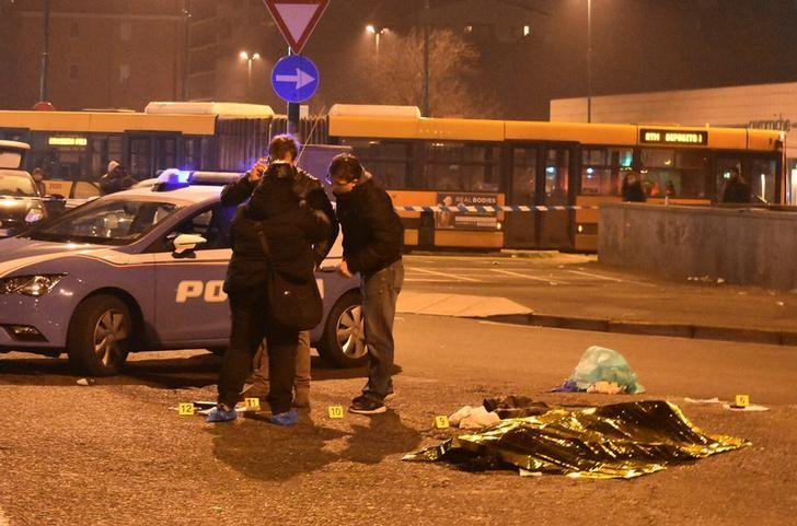 Italian Police officers work next to the body of Anis Amri, the suspect in the Berlin Christmas market truck attack, in a suburb of the northern Italian city of Milan, Italy December 23, 2016. REUTERS/Stringer