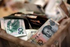 Las reservas de divisas de China bajaron en diciembre a cerca de su menor nivel de casi seis años, pero se mantuvieron sobre el nivel clave de 3 billones de dólares, ya que las autoridades del país intervinieron para apoyar al yuan antes de la asunción del presidente electo de Estados Unidos, Donald Trump. En la imagen, billetes chinos en la caja de cambio de un vendedor en un mercado de Pekín, el 14 de febrero de 2014.     REUTERS/Kim Kyung-Hoon/File Photo