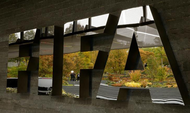 FILE PHOTO - A TV team is reflected in a logo of FIFA a meeting of the FIFA Council at its headquarters in Zurich, Switzerland October 13, 2016.  REUTERS/Arnd Wiegmann