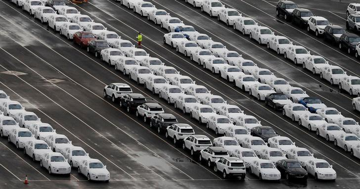 FILE PHOTO: A worker walks between rows of Jaguar and Land Rover cars as they wait to be shipped from Peel Ports container terminal in Liverpool, northern England, Britain December 9, 2016. REUTERS/Phil Noble/File Photo
