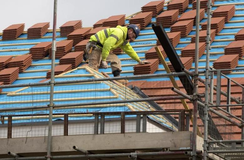 FILE PHOTO: A builder works on the roof of a new residential property development in north London, March 21, 2013.  REUTERS/Neil Hall/File Photo