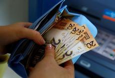 Женщина держит в руках белорусские рубли. Правительство Белоруссии готовит проект среднесрочного бюджета на ближайшие три года, опираясь на консервативный прогноз, который предполагает незначительные темпы роста экономики, замедление инфляции до 7,3 процента и снижение ставки рефинансирования до 10 процентов к концу 2019 года.   REUTERS/Vasily Fedosenko