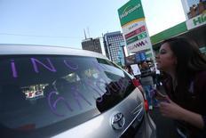 """Una manifestante escribe en el vidrio de un vehículo en Ciudad de México durante una jornada de protestas contra alzas estatales a las gasolinas, ene 4, 2017. México anunció el lunes un acuerdo para evitar incrementos """"injustificados"""" de precios de alimentos, bienes y servicios derivados en buena parte por el aumento de los precios de las gasolinas y diesel este mes, que ha generado malestar en amplios sectores de la sociedad y provocado protestas.  REUTERS/Edgard Garrido"""
