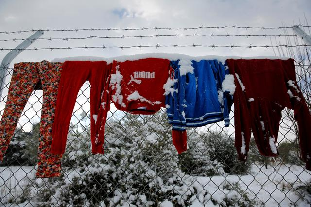 Clothes that belong to stranded refugees are covered with snow as they hang on a fence during a show storm at a refugee camp north of Athens, Greece January 10, 2017. REUTERS/Yannis Behrakis