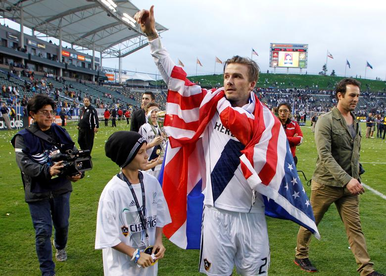 FILE PHOTO - Los Angeles Galaxy's David Beckham gives a thumbs up to the crowd next to his son Romeo after Galaxy defeated the Houston Dynamo to win the MLS Cup championship soccer game in Carson, California, U.S. on December 1, 2012.   REUTERS/Danny Moloshok