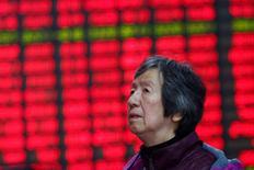 Un inversor mira las pantallas electrónicas que muestran información sobre las bolsas chinas en Shanghái, China. 3 de enero 2017.  Las acciones chinas cayeron por segundo día consecutivo el miércoles, presionadas por un aumento en la oferta de acciones y luego de que los inversores recogieron ganancias en los valores de las firmas de propiedad estatal. REUTERS/Aly Song - RTX2XBA1