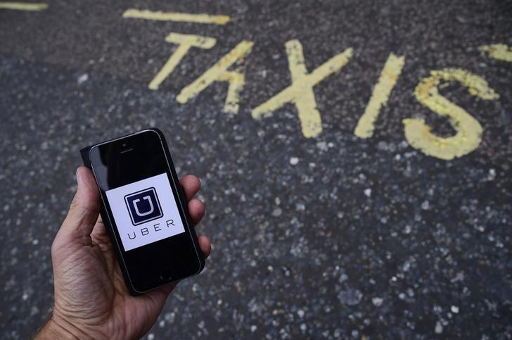 A photo illustration shows the Uber app logo displayed on a mobile telephone, as it is held up for a posed photograph in central London, Britain October 28, 2016. REUTERS/Toby Melville/Illustration - RTX2QV6Z