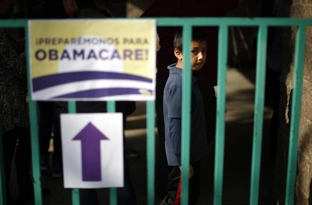 1月12日、米上院で医療保険制度改革(オバマケア)プログラムを無効にする法律案の策定を主要な委員会に指示する案が、51対48の賛成多数で可決された。今週中に下院へ回される。写真は健康保険手続きの登録イベントの列に並ぶ少年。カリフォルニア州カダヒーで2014年3月撮影(2017年 ロイター/Lucy Nicholson)