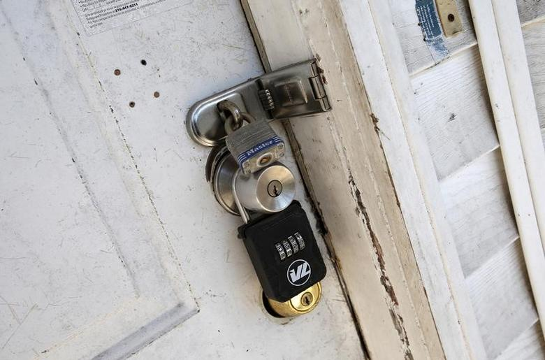 Locks are seen on the front door of an empty abandoned home in East Orange, New Jersey, March 25, 2015. REUTERS/Mike Segar