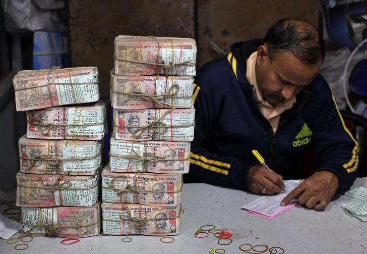 A bank employee fills a form after counting stacks of old 1000 Indian rupee banknotes inside a bank in Jammu, November 25, 2016. REUTERS/Mukesh Gupta/Files