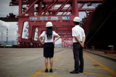 """Trabajadores se paran junto a un barco de carga en el puerto de Ningbo, provincia de Zhejiang, China. 21 de junio 2012. El Ministerio de Comercio de China dijo el jueves que """"tratará todos los métodos"""" para estabilizar el comercio en medio de lo que ve como una perspectiva comercial desafiante y complicada este año.REUTERS/Carlos Barria/File Photo"""