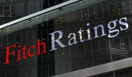 """Los planes de reducir impuestos del presidente electo de Estados Unidos, Donald Trump, podrían poner en riesgo la nota de crédito """"AAA"""" del país en el medio plazo, dijo el jueves Ed Parker, analista de calificación de deuda de la agencia Fitch. En la imagen de archivo, una bandera de Estados Unidos reflejada contra el logo de Fitch Ratings en su sede de Nueva York. REUTERS/Brendan McDermid"""