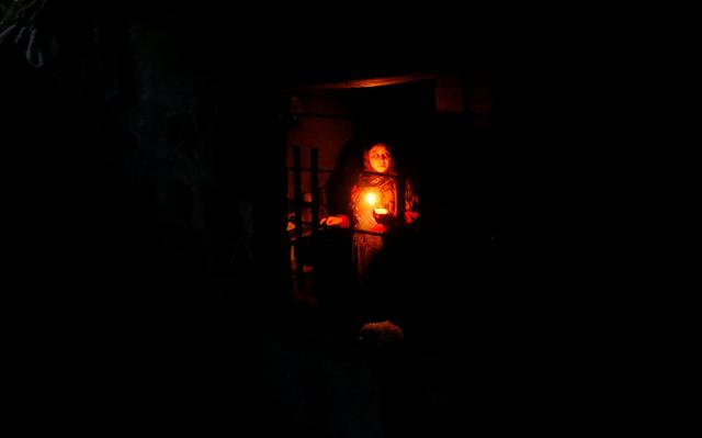 A Palestinian woman uses a candle light as she works in her kitchen during a power cut inside her house in Beit Lahiya in the northern Gaza Strip January 11, 2017. Picture taken January 11, 2017. REUTERS/Mohammed Salem