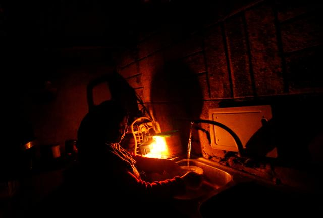 A Palestinian woman uses a candle light as she washes up in her kitchen during a power cut inside her house in Beit Lahiya in the northern Gaza Strip January 11, 2017. Picture taken January 11, 2017. REUTERS/Mohammed Salem