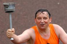 FILE PHOTO - Former England soccer manager Graham Taylor crosses the finish line of the 2004 London Marathon, Britain April 18, 2004. REUTERS/David Bebber/File Photo