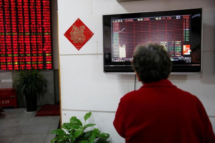 2017年1月3日,中国上海,一家券商营业部内股民看着电子显示屏上的股票信息。REUTERS/Aly Song