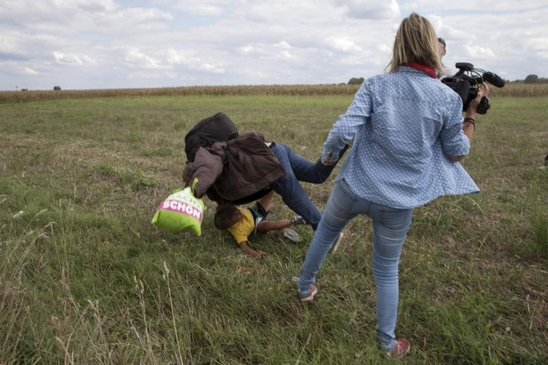 A migrant carrying a child falls after being tripped over by TV camerawoman (R) Petra Laszlo while trying to escape from a collection point in Roszke village, Hungary, September 8, 2015. REUTERS/Marko Djurica/Files